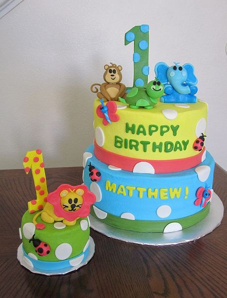 Two tier Safari theme first birthday cake with animals and matching mini cake